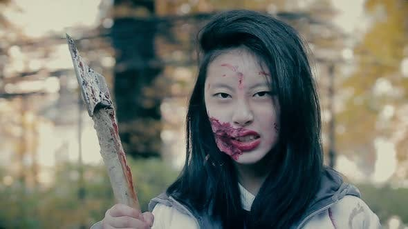 Thumbnail for Crazy Female Zombie Murderer With Bloody Axe Looking Aggressively Into Camera