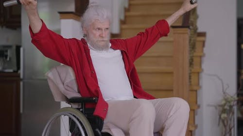 Confident Senior Disabled Handsome Man in Wheelchair Lifting Dumbbells in Slow Motion Indoors