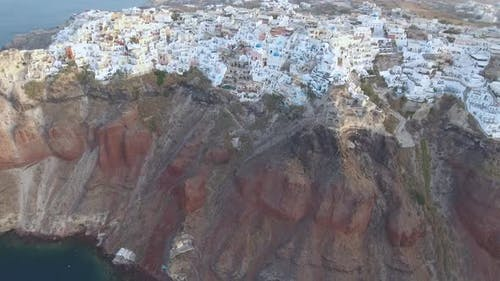 Flying over beautiful and famous Oia on Santorini Island in Greece during sunrise