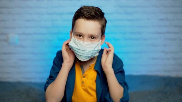 Teenage boy wearing medical mask to protect from infection of viruses