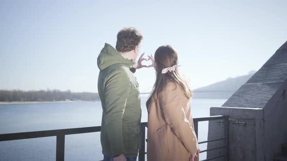 Cover Image for Happy Young Caucasian Man and Woman Making Heart Shape with Hands at the Background of Blue Autumn