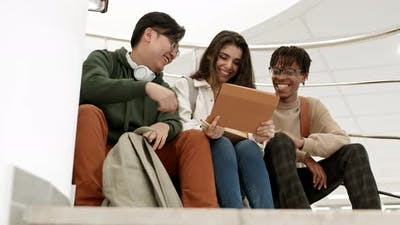Diverse College Friends Laughing with Tablet