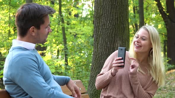Thumbnail for A Man and a Woman Sit on a Bench in a Park on a Sunny Day, the Woman Takes Pictures of Him