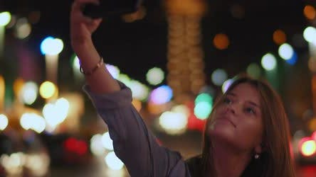 A young woman taking a selfie in the middle of the street, bokeh lights