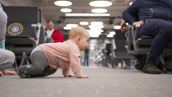 Little Baby Girl Crawling in the Airport Lounge