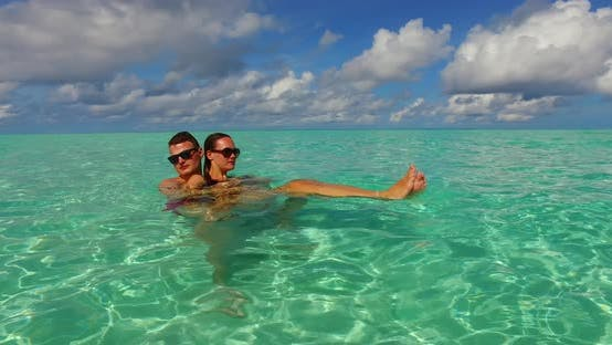 Fun man and woman in love dating on vacation have fun on beach on summer white sandy background 4K