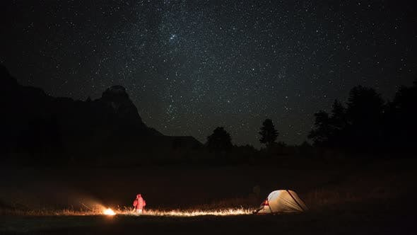 Time Lapse of Camping with a Man, Tent and Campfire at Night