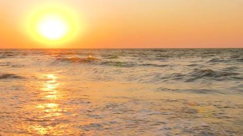 Colorful ocean beach sunrise with pastel palette sky and sun. Sunrise colors of sky, sea, ocean