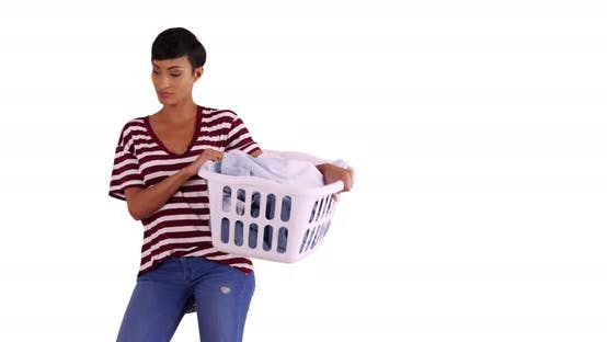 Thumbnail for Attractive black female holding basket of clean clothes in studio with copyspace