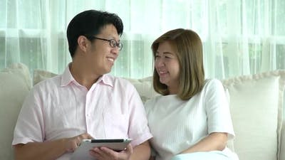 Asian Couple Using Tablet At Home