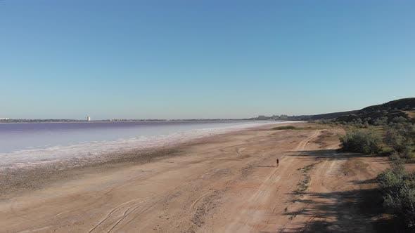 Thumbnail for woman rides on bike along coastline of Kuyalnik Liman