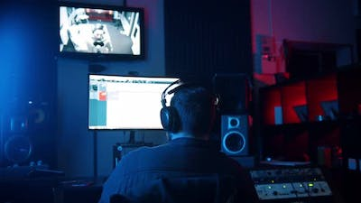 A Man Sound Engineer in Headphones Working in the Neon Sound Recording Studio - Recording a Rap