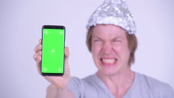 Thumbnail for Face of Stressed Young Man with Tinfoil Hat Showing Phone and Looking Scared