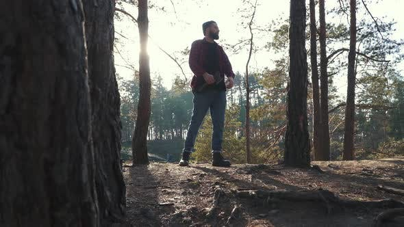 Cover Image for Young Bearded Man with an Axe Walk in Forest