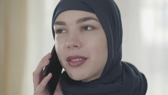 Thumbnail for Portrait of a Young Beautiful Muslim Woman in Black Headdress Talking By Cell Phone