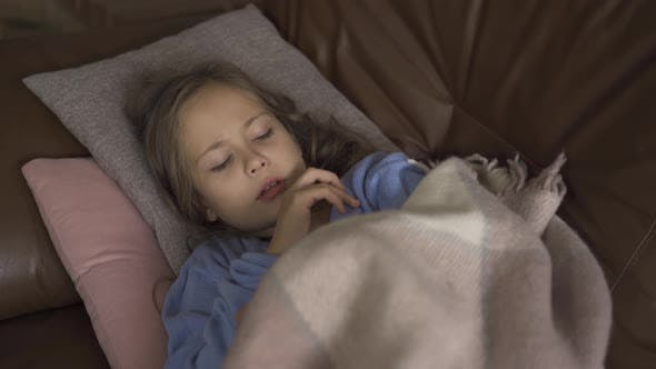 Thumbnail for Young Caucasian Girl in Blue Sweater Laying Under the Warm Blanket and Taking Temperature. Close-up