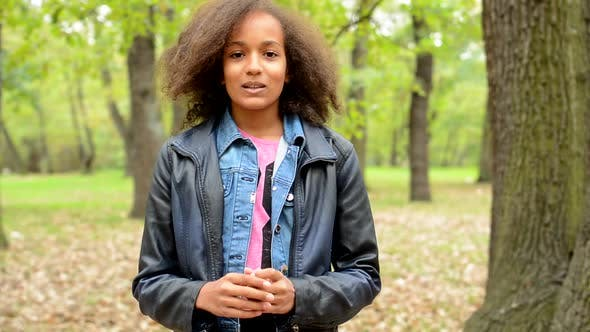 Thumbnail for Young Lively African Girl Talk About Herself in the Forest - Make Gestures with Hands - Eye Contact