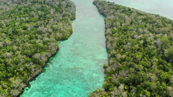 Aerial: flying over tropical sea pristine coastline rainforest turquoise lagoon
