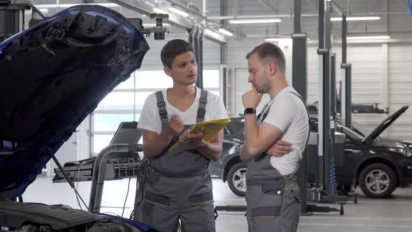 Thumbnail for Two Car Mechanics Discussing Automobile with Open Hood