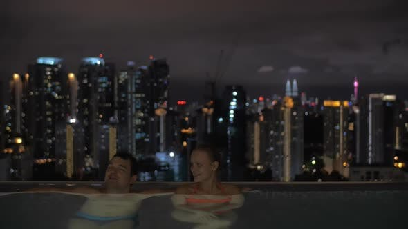 Thumbnail for Night View of Young Beautiful Couple in Swimming Pool on the Roof on Foreground and City Landscape