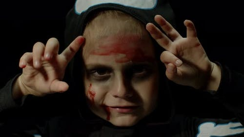 Хэллоуин, сердитая девушка с кровавым макияжем на лице. Малыш, одетый как страшный скелет, позирует, делает лица