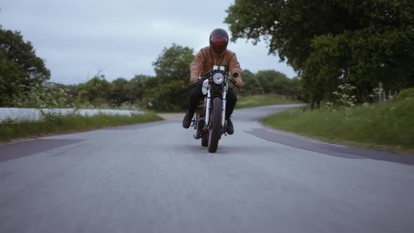 Tracking Shot of a Motorcycle Driven on a Tight Road on a Clear Skies