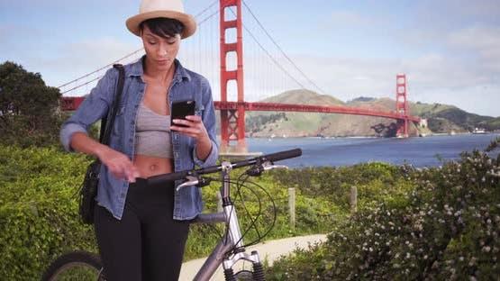 Black woman on bike in front of San Francisco Golden Gate Bridge using cellphone