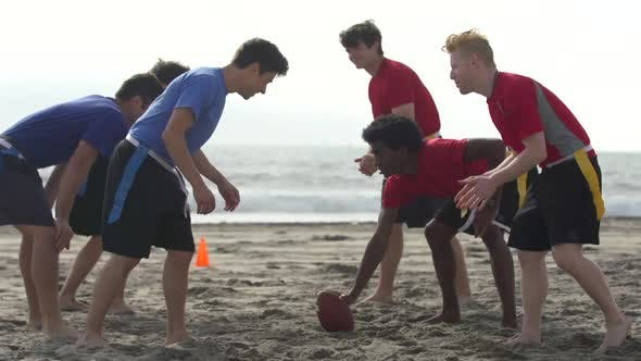 Thumbnail for A group of guys playing flag football on the beach.