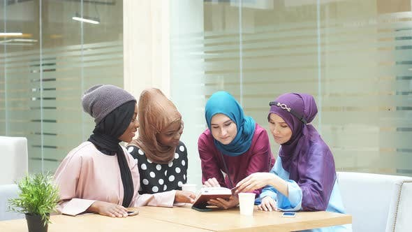 Thumbnail for Muslim Asian and African Women in Head Scarfs and Hijab Using Laptop in Cafe