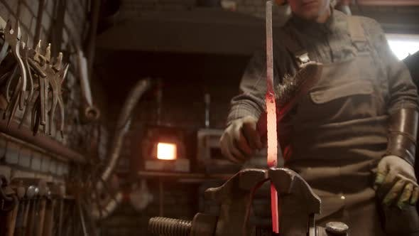 Thumbnail for A Man Blacksmith Forging a Twisted Piece of Metal Put in the Clamps