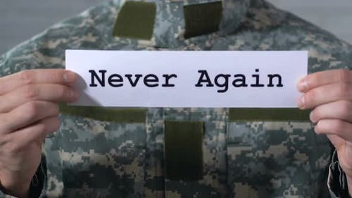 Never Again Written on Paper in Hands of Male Soldier, World Peace Concept