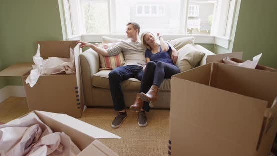 Thumbnail for Tired happy couple sitting on couch after unpacking
