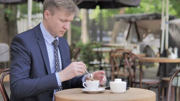 Thumbnail for Businessman Mixing Sugar and Drinking Coffee while Sitting in Outdoor Cafe