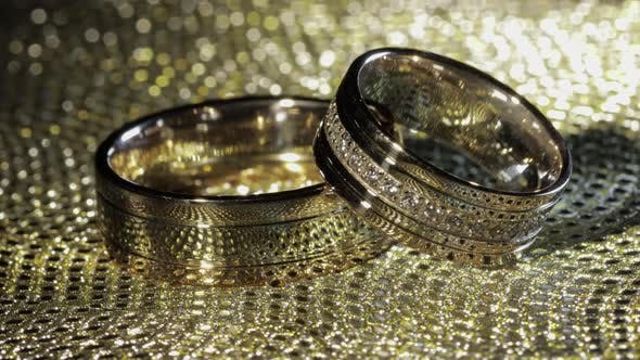 Thumbnail for Wedding Gold Rings Lying on Shiny Glossy Surface, Shining with Light, Close-up