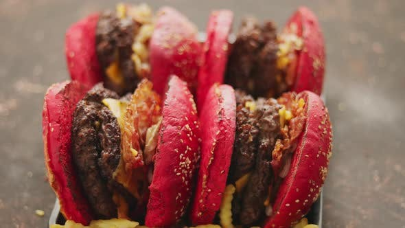 Cover Image for A Set of Red Bun Homemade Delicious Burgers of Beef, Bacon, Cheese, Grilled Onion on a Dark Rusty
