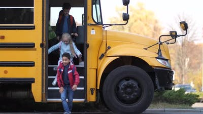 Female School Bus Driver Saying Bye To Schoolkids