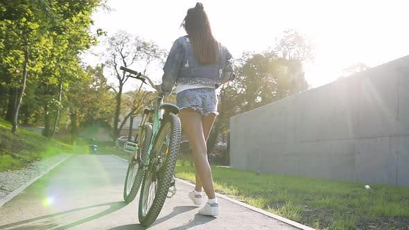Thumbnail for View from Back of Young Woman Walking on City Streets with Bicycle in Summer Day