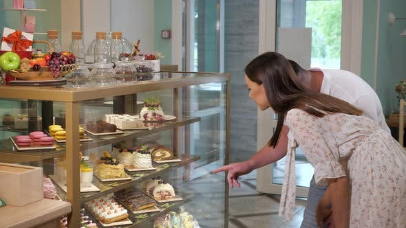 Girl and Guy Looks at Tasty Cakes in Shop Glass Show Case
