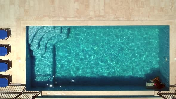 Thumbnail for Aerial view of young girl jumping into swimming pool.