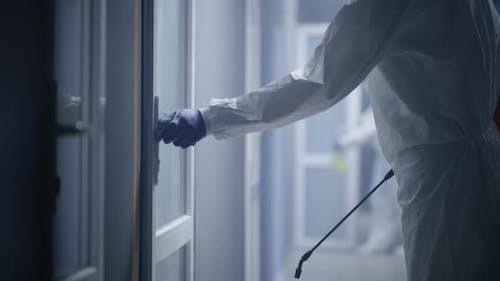 Men in Hazmat Suits Disinfecting Doors
