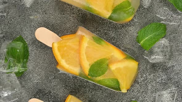 Fruit ice cream popsicles with fresh orange slices, green mint leaves and ice cubes rotating