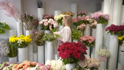 A Woman in a Flower Shop Collects a Bouquet
