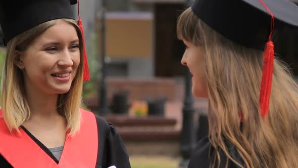 Thumbnail for Two Beautiful Students in Academic Dresses and Hats Discussing Future Plans