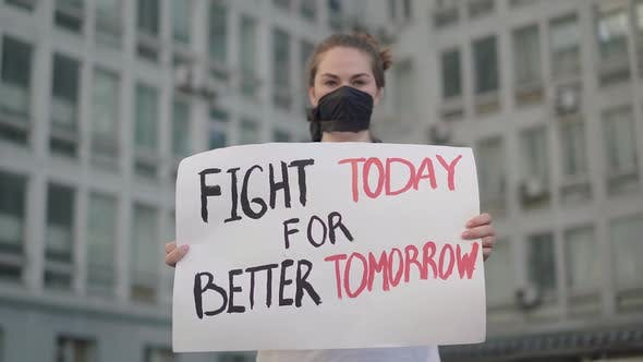 Thumbnail for Rack-Fokus ändert sich vom ernsten Gesicht des Aktivisten zu Banner mit Slogan. Seruious Schöne kaukasische