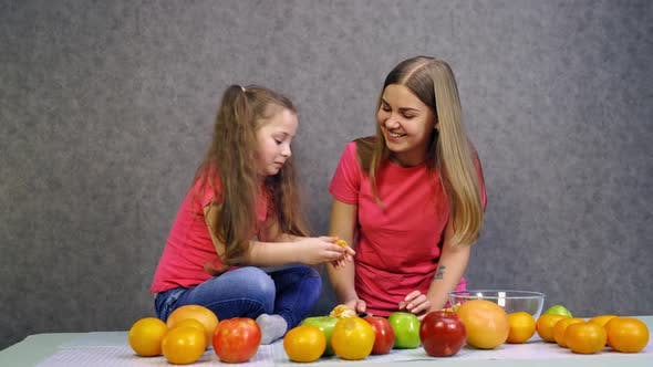 Thumbnail for Woman eating fruit with daughter. Happy woman eating orange with daughter at table