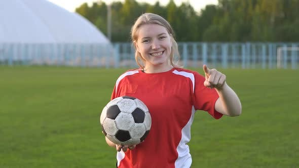 Young smiling girl football player holding soccer ball pointing with finger to the camera and to you