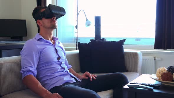 Thumbnail for Young Handsome Man Uses Virtual Reality Glasses in Home, in Living Room