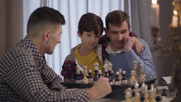 Thumbnail for Portrait of Happy Caucasian Grandfather and Grandson Playing Chess with Boy's Young Father