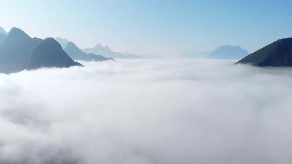 Thumbnail for Aerial drone flying over clouds morning fog mist covering valley in Laos