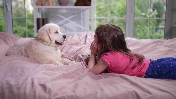 Thumbnail for Little Girl Lying on Cozy Bed with Puppy